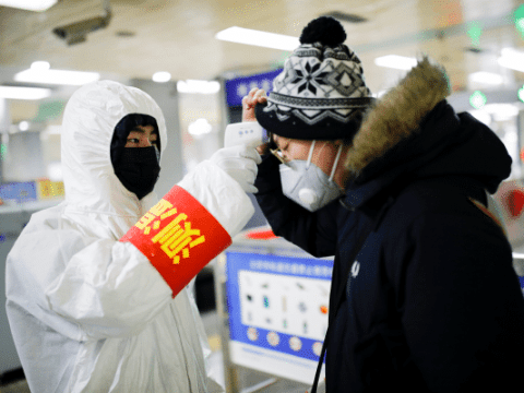 A passenger entering a Beijing subway station gets a temperature check on January 28. Photo: CNS/Reuters