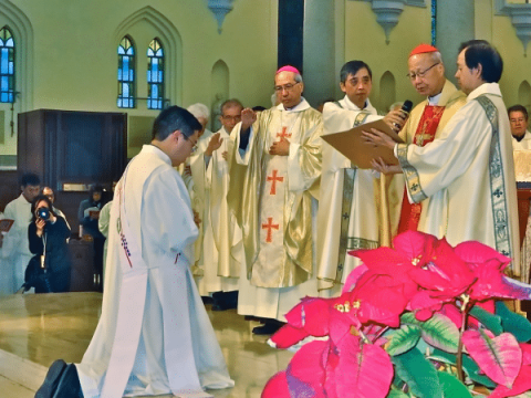 The imposition of hands by Bishop Ha and Cardinal Tong, together with other priests of the diocese, during Father Yan's ordination on January 4.