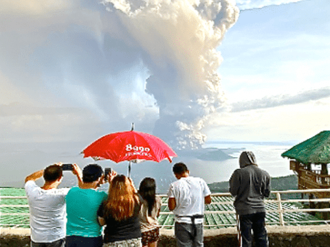 Tourists take pictures of Taal Volcano as it started spewing ashes into the air during its initial stage of eruption on January 12. Photo: UCAN/Joe Torres