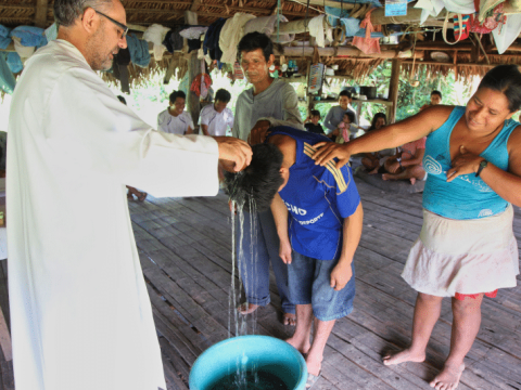 Augustinian Father Miguel Angel Cadenas baptises a young man in a village along the Urituyacu River in Peru. File photo: CNS
