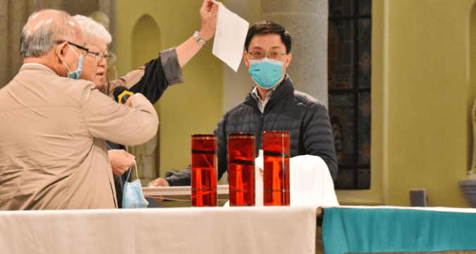 Father Thomas Law demonstrates how to place the face mask on a clean tray covered with tissue when a priest needs to remove it to take Communion at the altar.