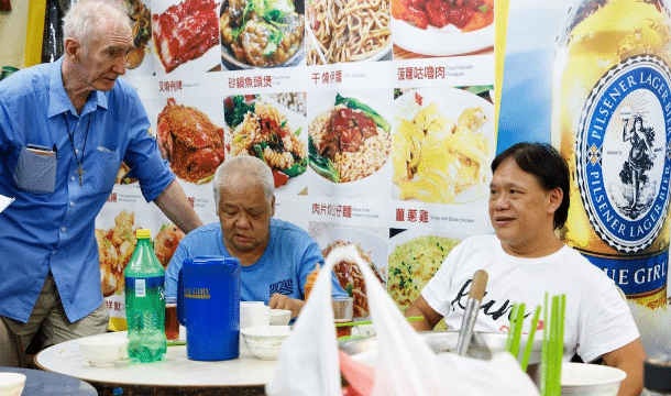 Father Wotherspoon (standing) with McRefugees at one of the Thursday Dinners MercyHK hosts for them. File photo: UCAN