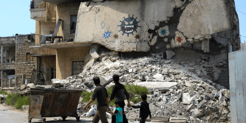 People walk past a damaged building with graffiti alluding to Covid-19 encouraging people to stay at home in Idlib, Syria on April 18. Photo: CNS/ Reuters
