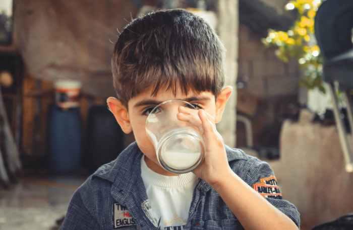 photo of boy drinking glass of milk