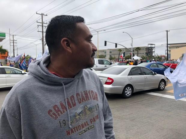 Eleuterio Juárez, migrante deportado, observa a los manifestantes afuera de la sede del segundo debate presidencial en la UABC.(Foto: Karla Amezola)