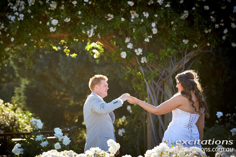 Bride and groom in a garden of white roses. Photo by Excitations, Mildura.