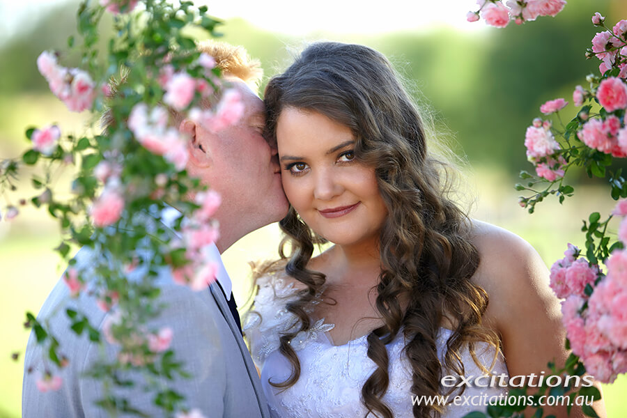Groom kissing bride amongst pink miniature roses. Amy and Tony's wedding by Mildura wedding photographers Excitations.