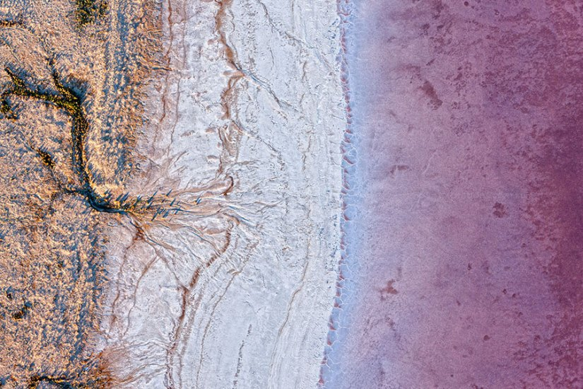Low altitude areial photograph of pink water and salt atLake Eyre South by Excitatiuons Stock Photos of Australia.