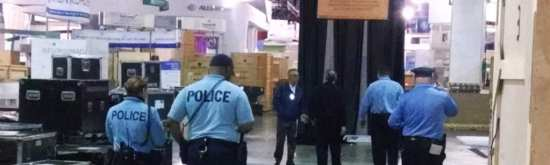 Authorities ID and escort unauthorized workers off show floor at Pennsylvania Convention Center.