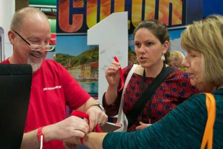 Jeff Bartle of 3D Exhibit helps visitors put on their RFID/NFC wristbands at EXHIBITORLIVE 2015.