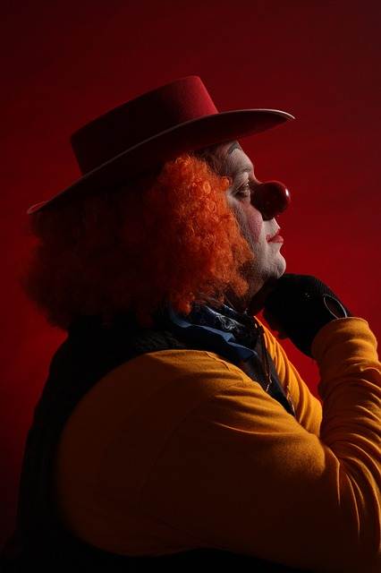 Clown in a red background looking off in the distance, as if pondering something.