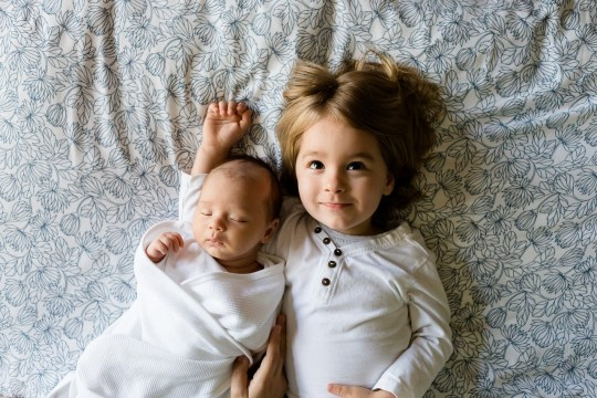 A newborn baby and toddler laying on the bed, looking up.