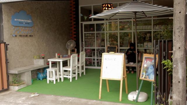 A coffee shop in Thailand with outdoor seating and a whiteboard menu.