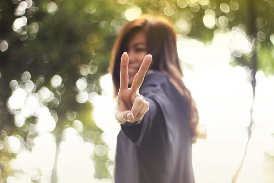 A Thai girl holding up the peace sign.