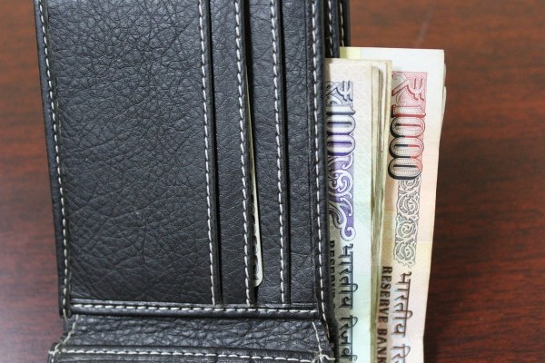 Indian Rupees tucked into a wallet.