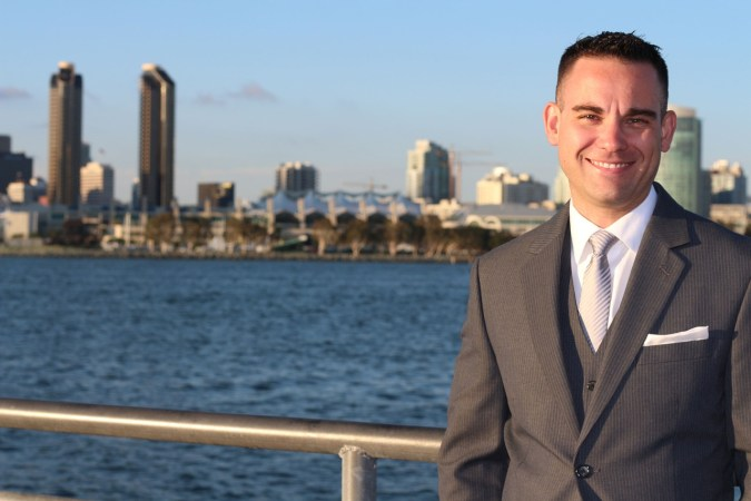 An insurance broker smiling in the foreground of a city.