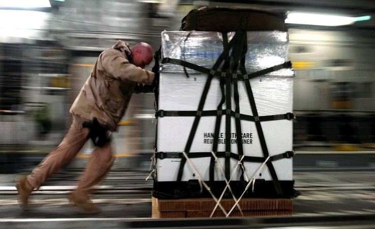 A man pushing a pallet of cargo.