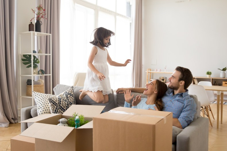 Family with young child and moving boxes in Switzerland apartment