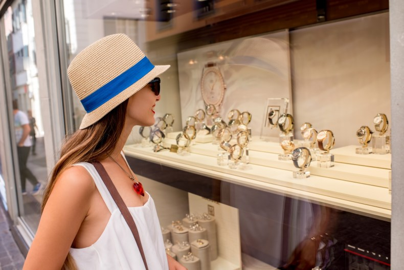 expat Switzerland, woman looks at Swiss watches on display while shopping