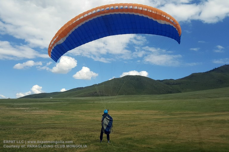 student with paragliding wings practicing ground handling
