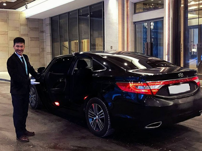 Chauffeur holding open door of black sedan