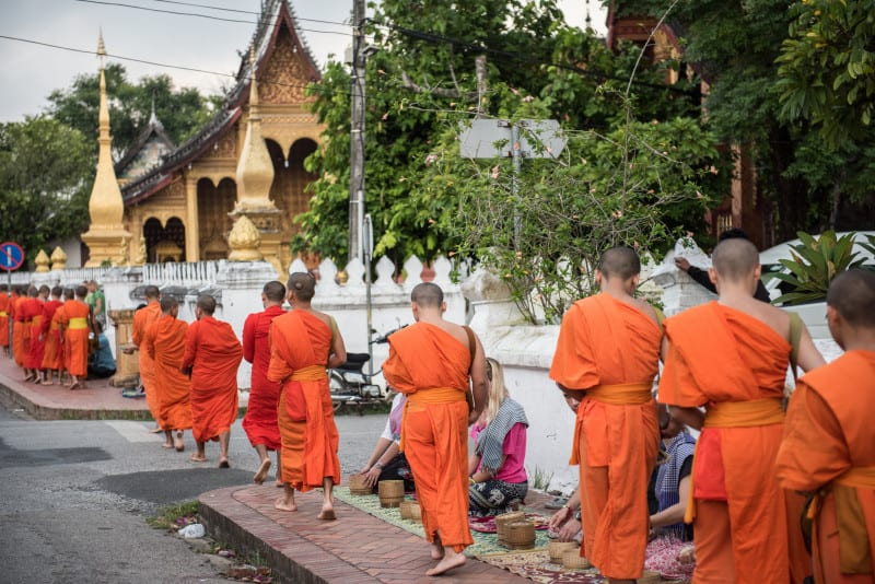 Monks walking in the complex of Wat Xieng Thong. Wat Xieng Thong is the oldest temple in Laos and is one of the most important buddhist shrine among all other Lao monastries.