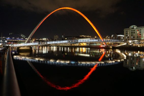 Millennium bridge in Newcastle at night, city lights are reflected off the water