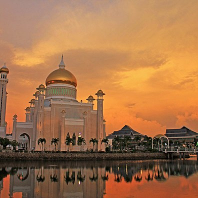 Bandar seri Begawan, Brunei. The flamboyant sunset greatly enhances the beauty of the mosque and its reflection in the water.