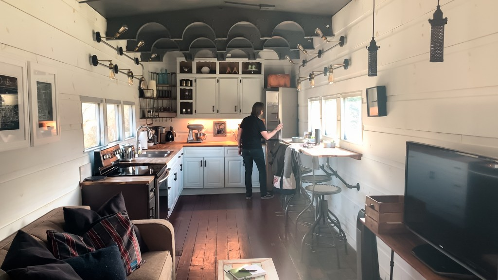 the living room and kitchen inside a train car airbnb