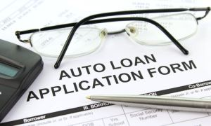 car loan form with glasses and pen