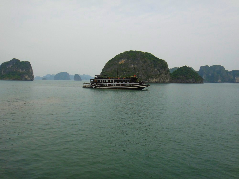 1-a-traditional-wooden-junk-floats-peacefully-on-bai-tu-long-bay