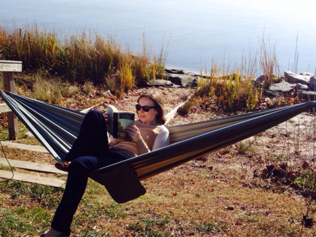 reading a book while relaxing in a hammock