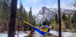 Jess hanging out in a golden state serac camping hammock while enjoying a view of half dome in yosemite national park