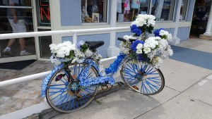 Shows a bike decorated with blue and white flowers in Tarpon Springs