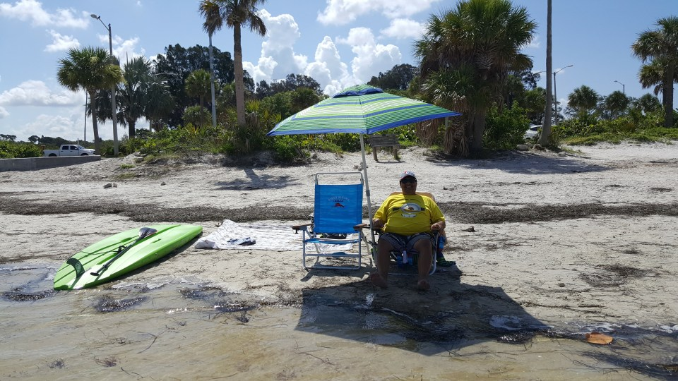 shows a man under a beach umbrella at secluded Sunset Beach in Tarpon Springs, FL