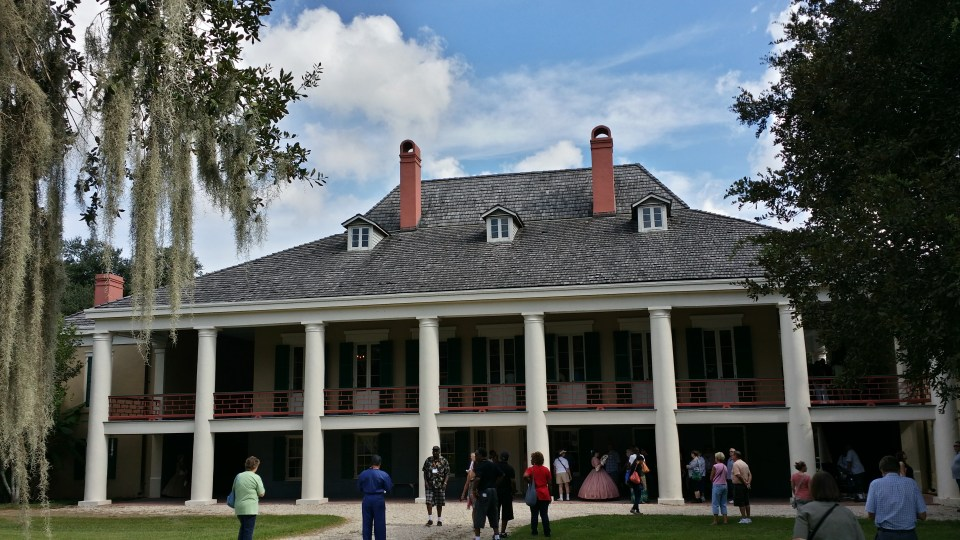 shows the front of Destrehan Manor House with people on antebellum dress