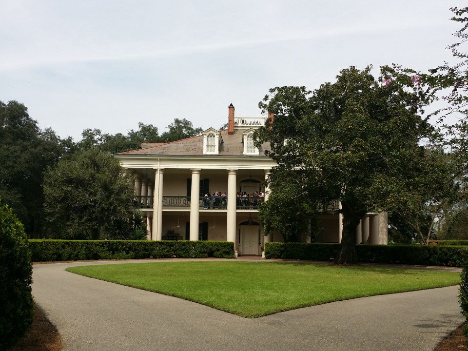 shows the outside of Oak Alley Plantation with people on the second floor veranda