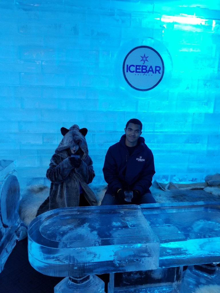 Shows two children sipping drinks at Orlando's Ice Bar. The young girl is wearing a borrowed cheetah coat. The table in the foreground is made of ice