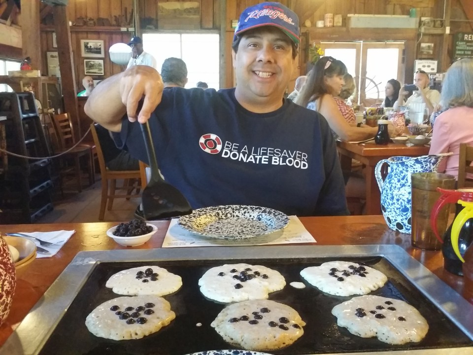 Shows a man cooking pancakes on his tabletop griddle as part if a unique breakfast experience as discussed in our road trip guide