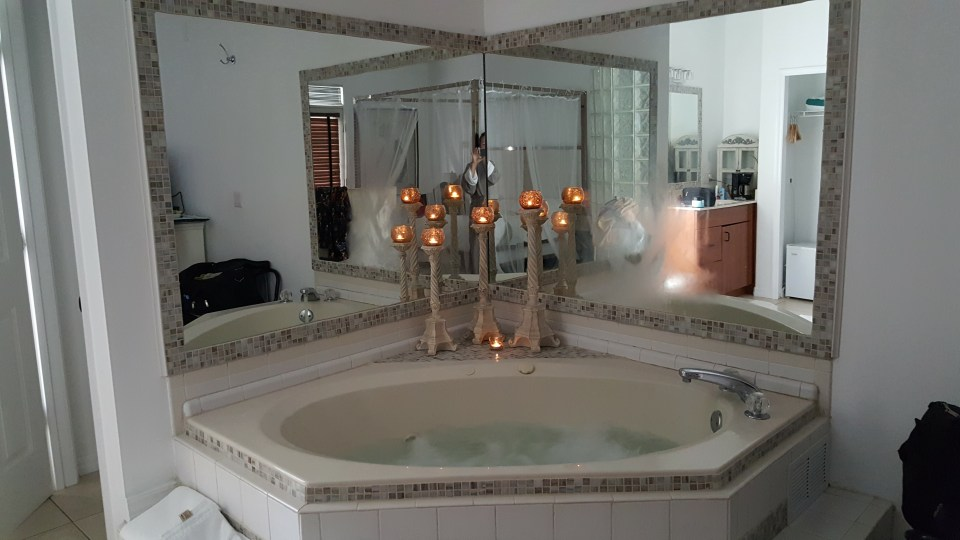 picture of a two person Jacuzzi with lit candles and mirrored walls at the romantic White Orchid Inn