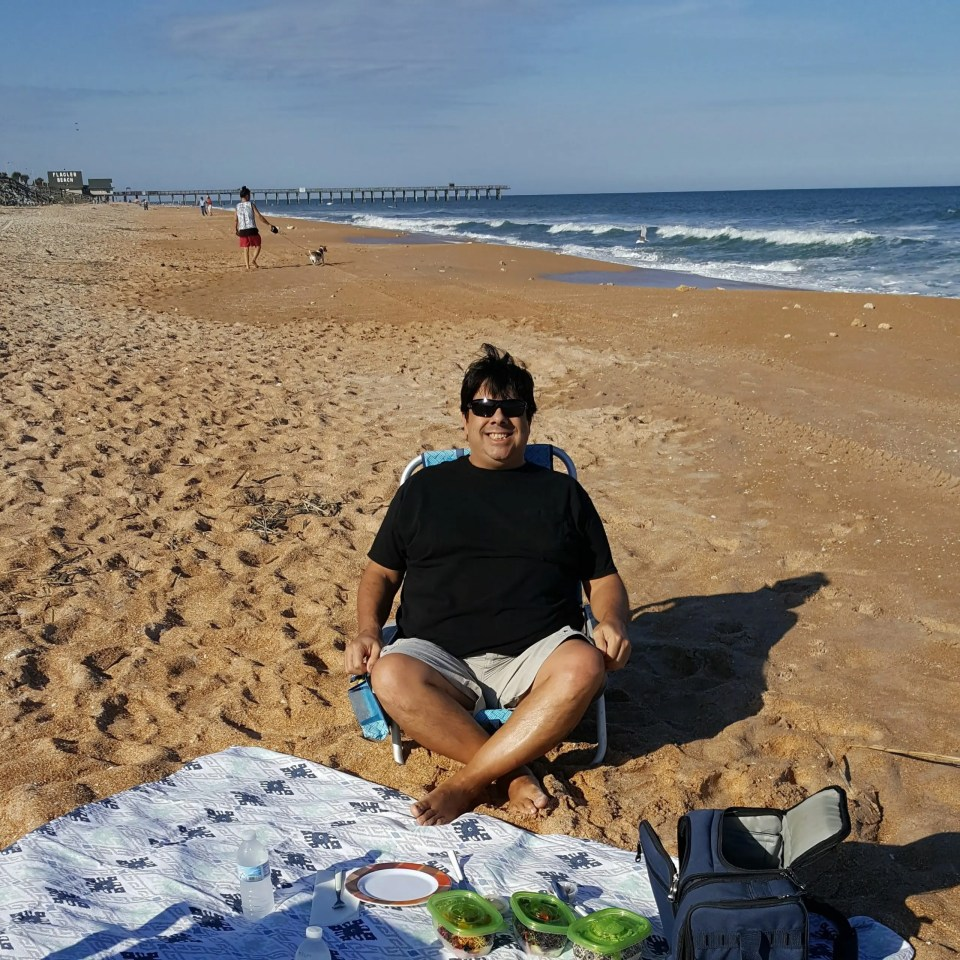 a man sitting on a beach chair in front of a blanket spread out before him with a picnic lunch on Flagler Beach