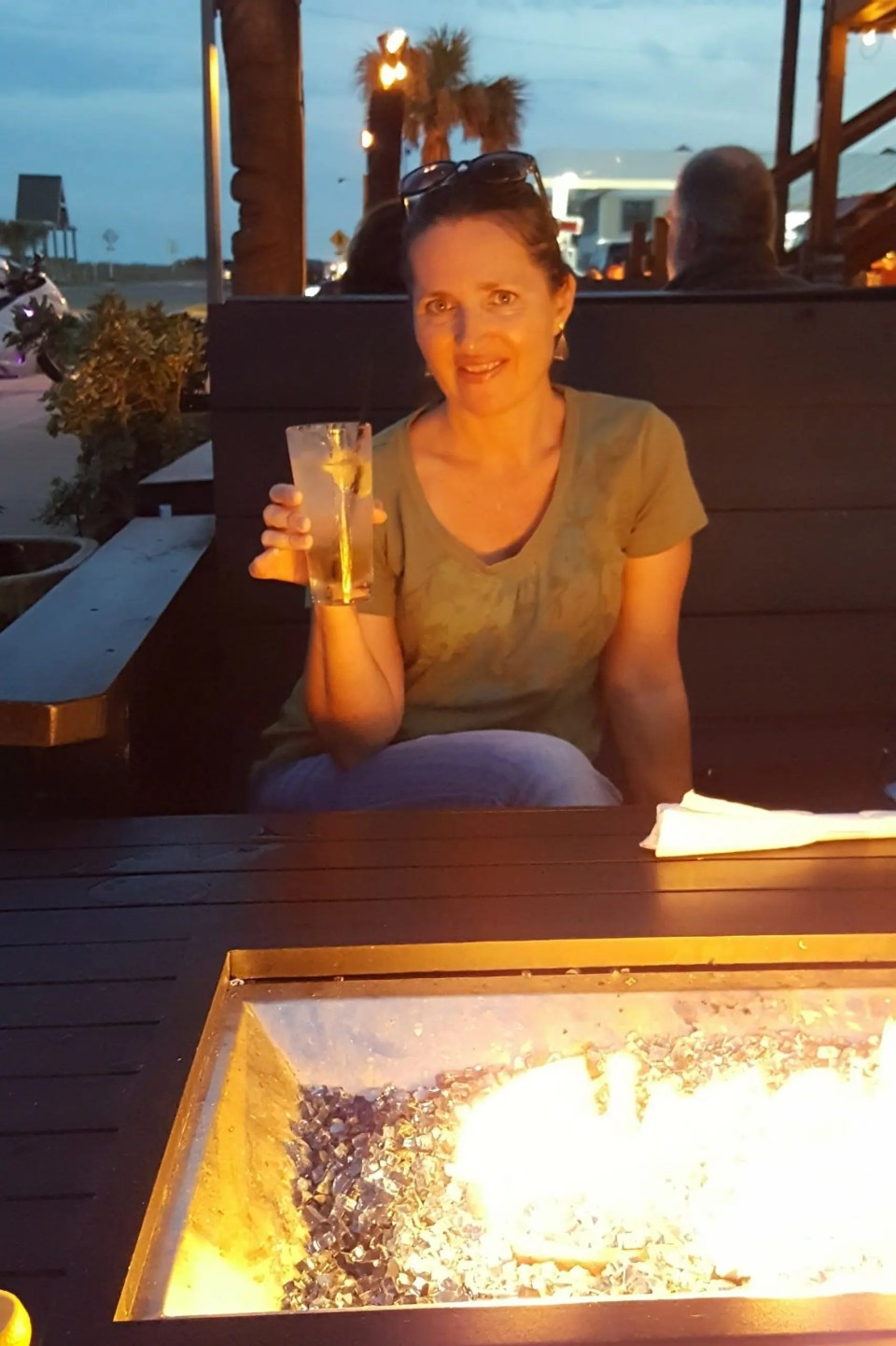 a woman sitting at an outdoor table drinking a beverage in front of a table top fire pit