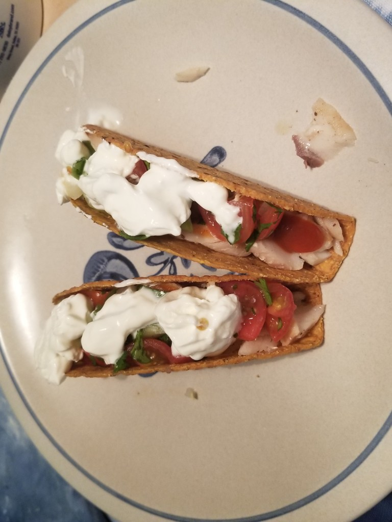 Shows two fish tacos in corn tortillas  on a plate