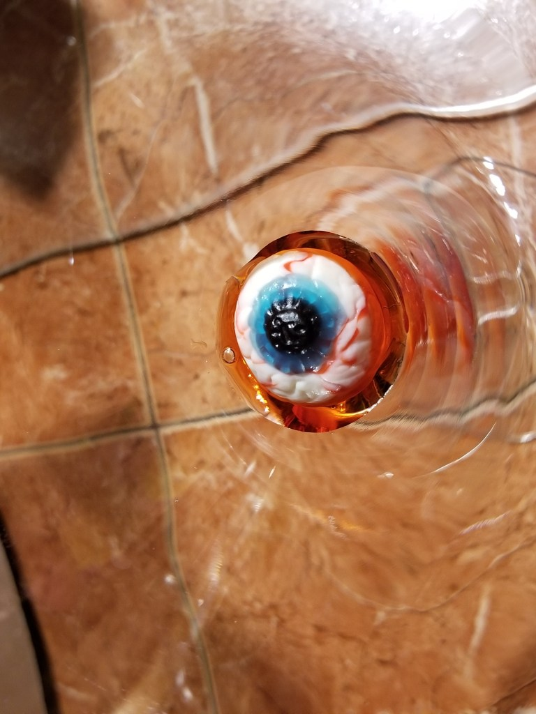 gummy eyeball placed in the bottom of a martini glass on top of grenadine so it looks like blood