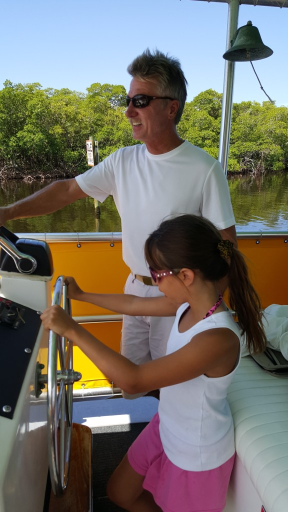 shows a girl steering a boat in Sanibel Florida