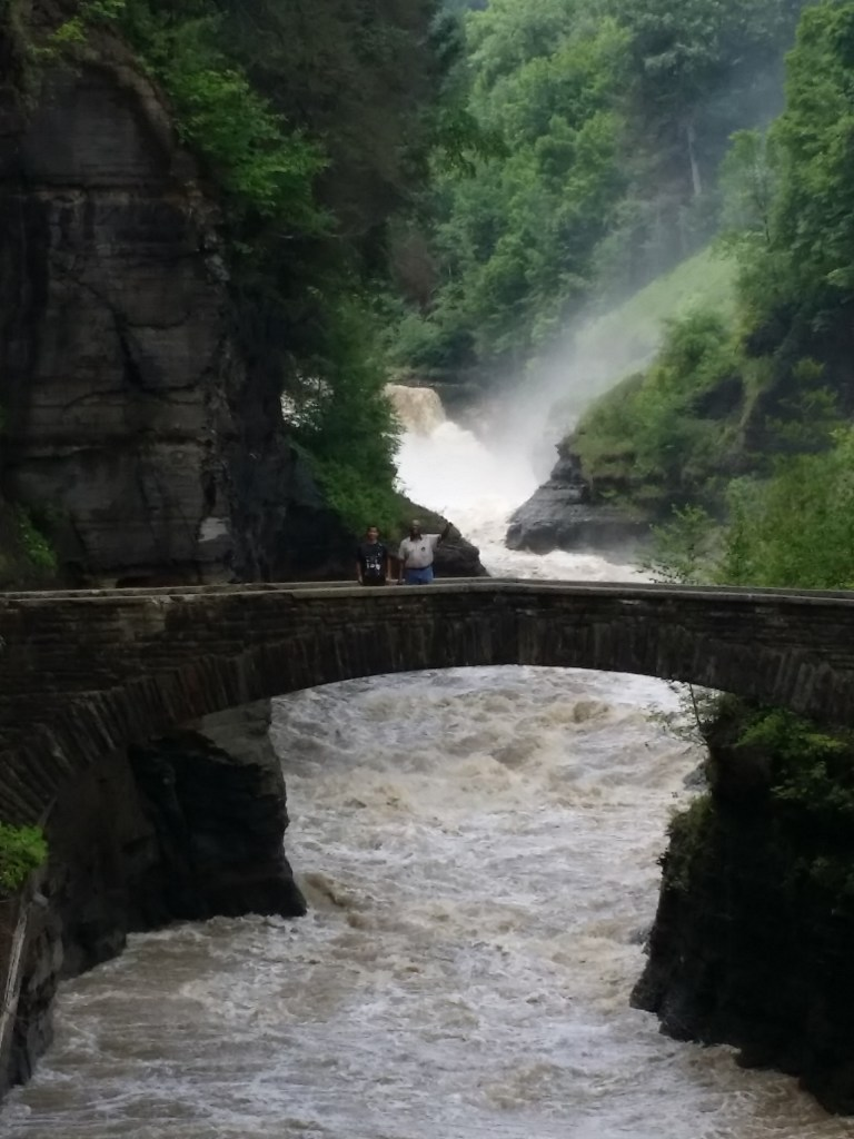 shows two people standing on a rock bridge in Letchworth State Park New York