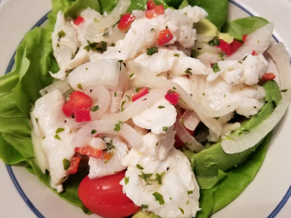 best ceviche recipe served on a bed of lettuce with avocados, onions, and grape tomatoes