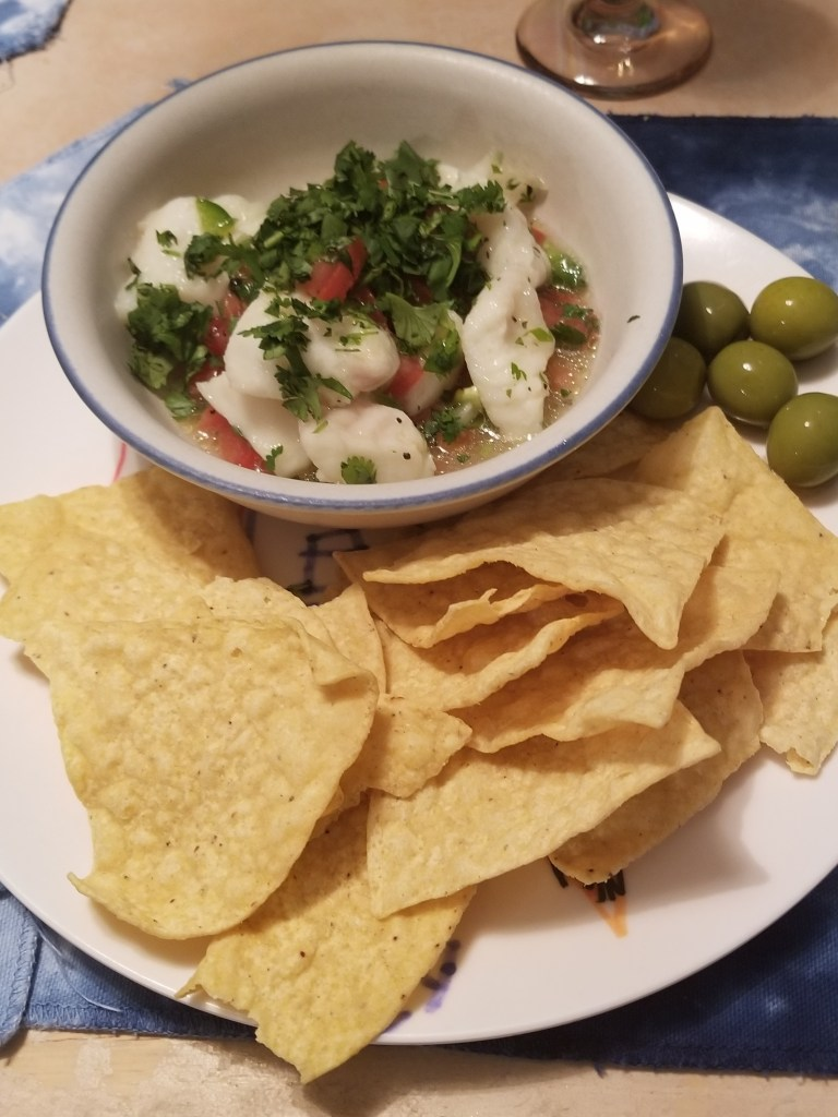 best ceviche recipe topped with cilantro and served with tortilla chips and green olive