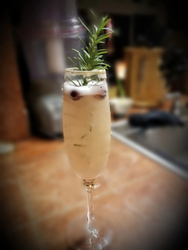 New Year's cocktails: Champagne glass with a small amount of cranberry simple syrup filled with Champagne, garnished with frozen cranberries and a rosemary sprig