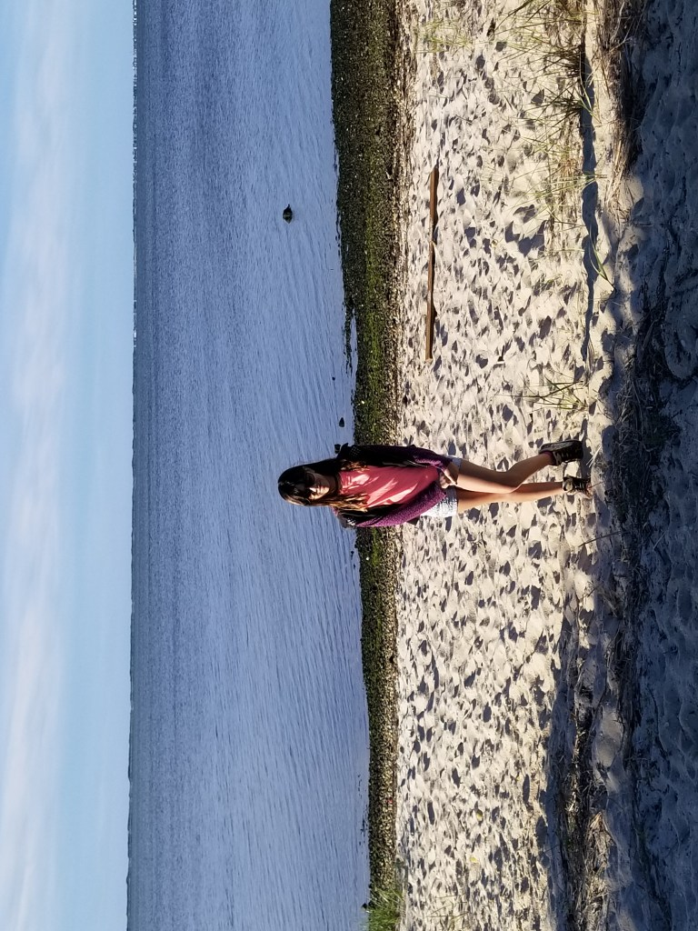a girl stands posing on the beach in South Shore Long Island